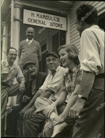 Nancy Olson talking with a group of men at H Margulies General Store, United States, 1950.