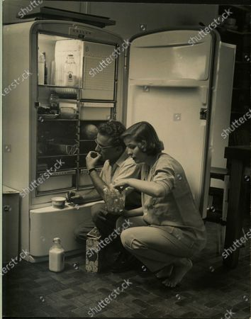 American actress Nancy Olson eating some snacks from the refrigerator with husband, Alan Jay Lerner, United States, 1950.