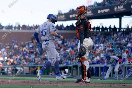 Los Angeles Dodgers' Matt Beaty (45) scores a run past San Francisco Giants catcher Buster Posey (28) on a single by DJ Peters during the seventh inning of a baseball game, in San Francisco