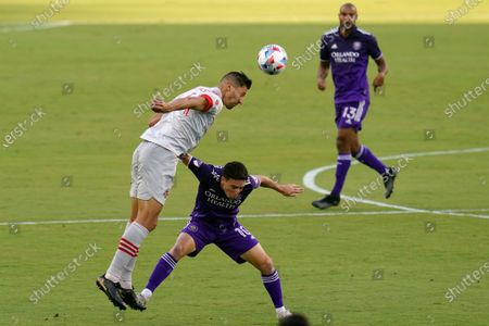 Toronto FC defender Omar Gonzalez, left, heads the ball away from Orlando City midfielder Mauricio Pereyra (10) during the first half of an MLS soccer match, in Orlando, Fla