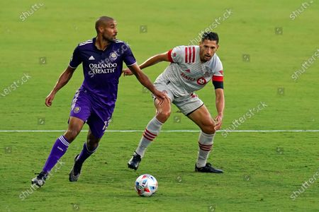 Orlando City forward Tesho Akindele, left, looks to pass the ball as Toronto FC defender Omar Gonzalez defends during the first half of an MLS soccer match, in Orlando, Fla