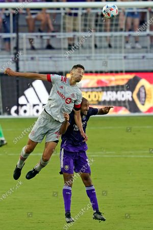 Toronto FC defender Omar Gonzalez, left, and Orlando City forward Tesho Akindele battle for position for a head ball during the first half of an MLS soccer match, in Orlando, Fla