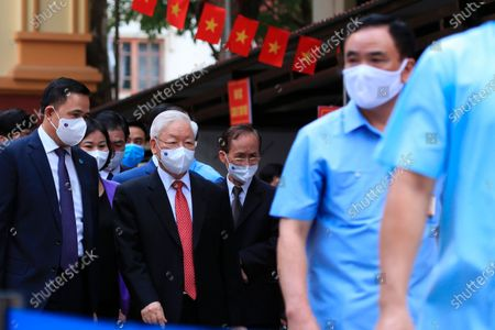 Vietnam's Communist Party General Secretary Nguyen Phu Trong, center left, leaves a polling station after voting in Hanoi, Vietnam . Vietnamese cast their ballots to elect 500 delegates for a five-year term at the National Assembly, Vietnam's legislative body, as the country is combating a new wave of COVID-19