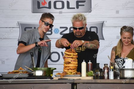 Stock Picture of Hunter Fieri, left, watches his father Guy Fieri build a tower of food at the Food Demonstration event during the Grand Tasting at the South Beach Wine and Food Festival in Miami Beach, Florida, USA - 22 May 2021