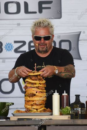Stock Image of Guy Fieri builds a tower of food at the Food Demonstration event during the Grand Tasting at the South Beach Wine and Food Festival in Miami Beach, Florida, USA - 22 May 2021