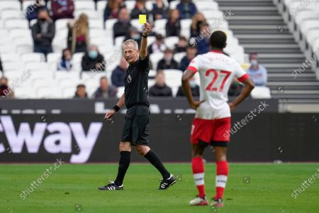 Referee Martin Atkinson presents a yellow card to Ibrahima Diallo of Southampton for a foul on Jarrod Bowen of West Ham United