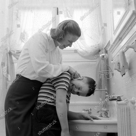 Stock Picture of Governor Gerhard Mennen's wife, Nancy Williams Gram, cleaning her son's ears, United States, March 1949.