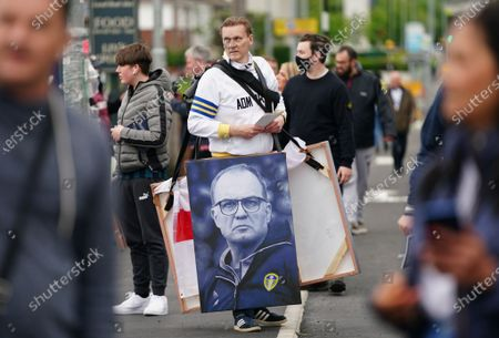 A fan holds a portrait of Leeds United's manager Marcelo Bielsa before the English Premier League soccer match between Leeds United and West Bromwich Albion in Leeds, Britain, 23 May 2021.