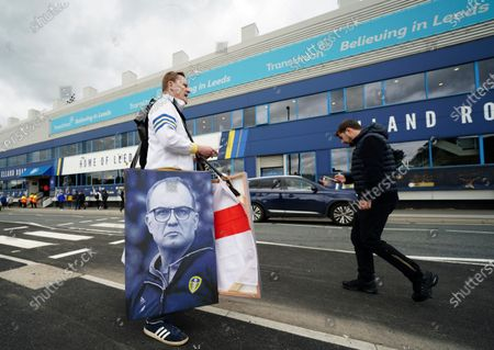 Vendor displays posters of Leeds United's head coach Marcelo Bielsa before the English Premier League soccer match Leeds United and West Brom at Elland Road in Leeds, England
