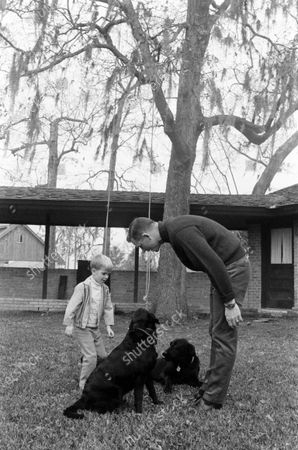 David Randolph Scott and his child playing with a dog, United States, March 1969.