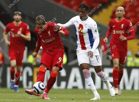 Liverpool's Roberto Firmino (L) in action against Crystal Palace's Wilfried Zaha (R) during the English Premier League soccer match between Liverpool FC and Crystal Palace in Liverpool, Britain, 23 May 2021.