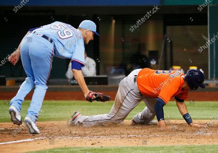 Stock Photo of Houston Astros' Jason Castro, right, avoids a tag by Texas Rangers relief pitcher Brett de Geus, left, as he scores on a wild pitch during the eighth inning of a baseball game in Arlington, Texas