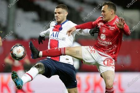 PSG's Mauro Icardi, left, is challenged by Brest's Julien Faussurier during the French League One soccer match between Brest and Paris Saint-Germain at the Stade Francis-Le Ble stadium in Brest, France