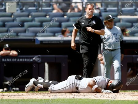Chicago White Sox catcher Yermin Mercedes (R) lays on the ground as a trainer (Top-Center) and Chicago White Sox manager Tony La Russa (R) after getting hit in the helmet by a pitch by New York Yankees starting pitcher Jameson Taillon (Not Pictured) in the fourth inning of their MLB game in the Bronx, New York, USA, 23 May 2021.