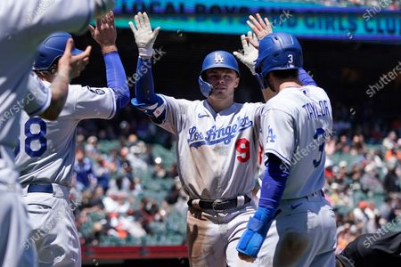 Los Angeles Dodgers' Gavin Lux, center, is congratulated by DJ Peters, left, and, Chris Taylor after hitting grand slam home run against the San Francisco Giants during the third inning of a baseball game in San Francisco