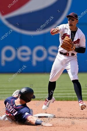 Cleveland Indians' Cesar Hernandez looks toward first base after getting Minnesota Twins' Max Kepler out at second base in the in the fifth inning of a baseball game, in Cleveland. Miguel Sano was safe at first base