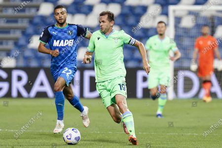 Sassuolo's Jeremy Tolja  (L) and Lazio's Senad Lulic (R) in action during the Italian Serie A soccer match US Sassuolo vs SS Lazio at Mapei Stadium in Reggio Emilia, Italy, 23 May 2021.