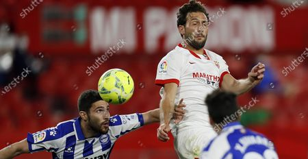 """Stock Image of Sevilla´s Argentinian midfielder Franco Vazquez (R) jumps for the ball with Alaves´ defender Alberto Rodriguez """"Tachi"""" (L) during a Spanish LaLiga soccer match between Sevilla FC and Alaves at Sanchez Pizjuan stadium in Sevilla, southern Spain, 23 May 2021."""