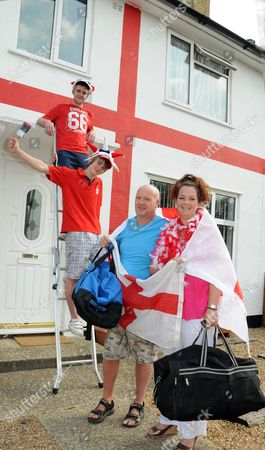 Andy Munro and his wife Sarah with Sarah's sons Orrin (19) and Tyler (17) in front of their home, which has been painted to resemble a giant England flag