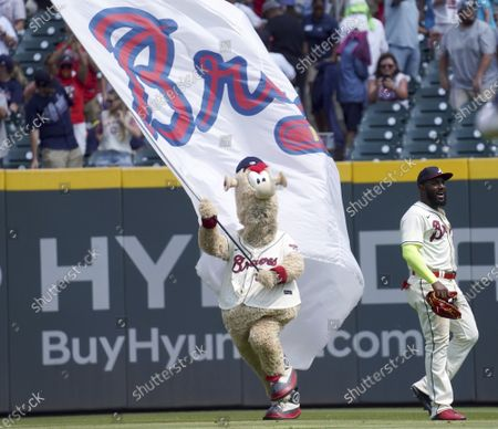 Stock Photo of Atlanta Braves' mascot Blooper runs past outfielder Marcell Ozuna at the end of a baseball game against the Pittsburgh Pirates', in Atlanta. The Braves' defeated the Pirates' 7-1