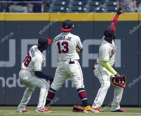 Stock Picture of Atlanta Braves' outfielders Guillermo Heredia (38), Ronald Acuna Jr. (13) and Marcell Ozuna (20), pose for a selfie at the end of a baseball game against the Pittsburgh Pirates', in Atlanta. The Braves' defeated the Pirates' 7-1