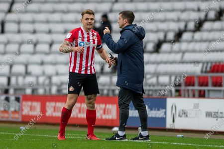 Stock Photo of Max Power celebrates with Andrew Taylor, first team coach after scoring his sides first goal of the match during the Sky Bet League 1 match between Sunderland and MK Dons at the Stadium Of Light, Sunderland on Saturday 14th November 2020.