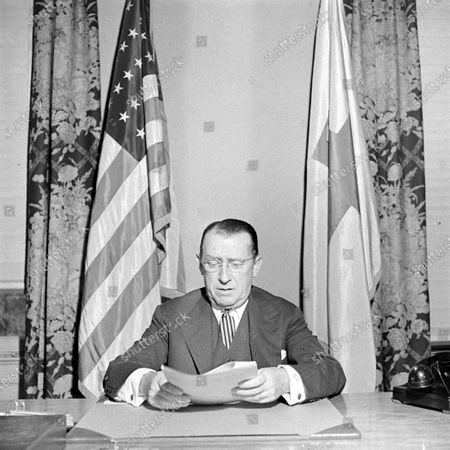 President of the American Red Cross Daniel Basil O'Connor sitting while reading at the table, August 1944.