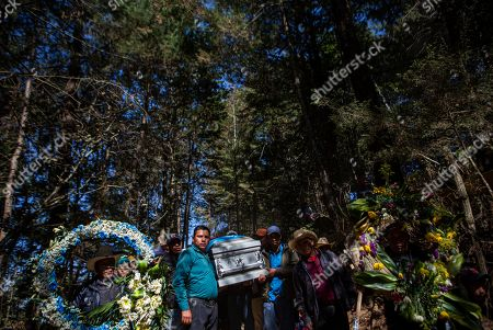 People carry a coffin with the remains of Rivaldo Jimenez, one of the Guatemalan migrants who was killed near the U.S.-Mexico border in January, at a cemetery in Comitancillo.