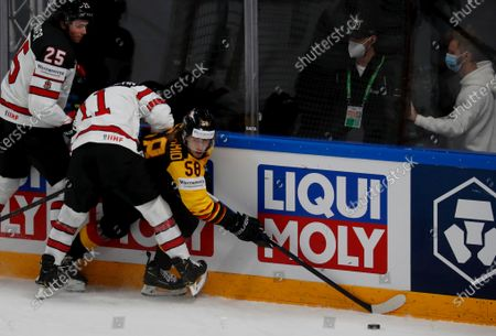 Markus Eisenschmid (R) of Germany and Owen Power (L) and Jaret Anderson-Dolan of Canada in action during the IIHF 2021 World Ice Hockey Championships group B match between Germany and Canada at the Arena Riga, Latvia, 24 May 2021.
