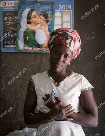 """Olive Nyakato is 24 years old. She's celibatary and childless. She lives alone in the bush a few miles from Buliisa. Faced with the Tilenga oil project led by Total, the CNOOC and the Ugandan government, it has the same demands as its refractory colleagues. â You understand, I n†have more resources with my harvesting, we n†have the right than to grow crops with a short cycle, less than 6 months. Here with sandy soil, we can't grow much and casava (cassava), our staple food, requires one to three years before we can be harvested. I n†have received no compensation for three years neither for my land nor for my harvestments. And their compensation rate is too low!  Olive signed a petition with 490 other people claiming their dedication to the French oil company Total. This petition was submitted on 24 January 2021 and handed over to Total, in its offices in Kampala by a delegation of which Olive was a member. Very pious, Olive was absolutely able to pose with his little statue of the Virgin Mary, as a prayer sent to Total for a fair settlement of their disputes. With Total's money, Olive dream of resuming its interrupted and confit studies: â L' education is not yet stop ever.- Buliisa, Buliisa, Buliisa District, Uganda, March 2021.  -  Olive Nyakato is 24 years old. She is single and has no children. She lives with her mother in the bush a few kilometers from Buliisa. Facing with the Tilenga oil project, leads by Total, CNOOC and the Ugandan government, she has the same demands as her refractory colleagues support by local and international NGOs. """"You see, I have no more resources with my crops, we are only allowed to grow crops with a short cycle, less than 6 months. Here with the sandy soil we can't grow much and the cassava, our staple food, takes one to three years before it can be harvested. I have not received any compensation for th"""