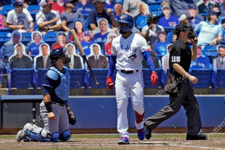 Toronto Blue Jays' Lourdes Gurriel Jr. flips his bat after his solo home run off Tampa Bay Rays starting pitcher Ryan Yarbrough during the fourth inning of a baseball game, in Dunedin, Fla. Looking on are catcher Mike Zunino, left, and home plate umpire Junior Valentine