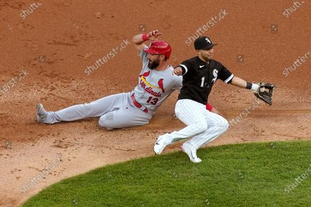 St. Louis Cardinals' Matt Carpenter, left, steals second as the throw from Chicago White Sox catcher Yasmani Grandal pulls Nick Madrigal, right, away from the bag during the second inning of an interleague baseball game, in Chicago