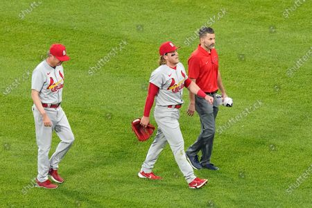 St. Louis Cardinals' Harrison Bader, center, leaves the game with manager Mike Shildt, left, and a member of the training staff after Bader was unable to make a diving catch of a shallow fly ball by Chicago White Sox's Nick Madrigal during the third inning of an interleague baseball game, in Chicago