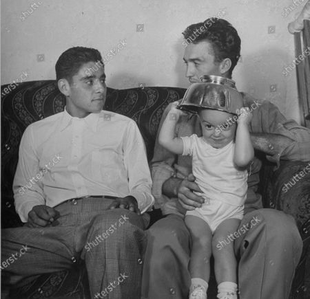 Pancho Gonzales (L) sitting with a man holding a child, September 1948.