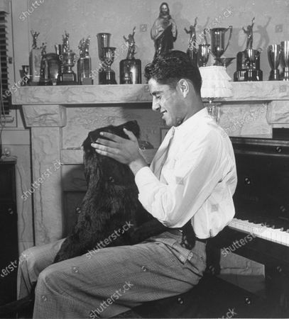 Pancho Gonzales playing with a dog, September 1948.