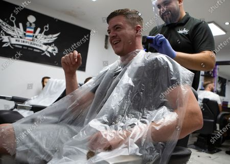 Stock Image of A man getting his hair cut at Mr Snips Barber Shop. Barbers' Shops and Hairdressers reopen across England after being closed since March due to the Lockdown imposed by the UK Government to help curb the spread of the COVID-19 pandemic In Stanford Le Hope, England on July 4, 2020.