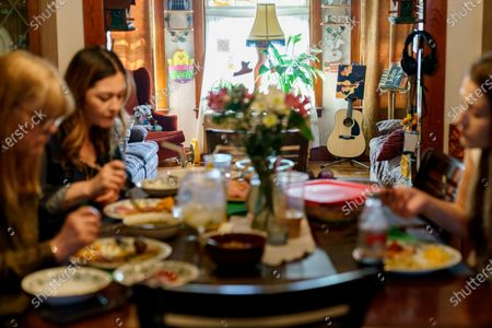 """The guitar and photo of John McCarthy are displayed as his wife, Christine, 65, left, sits down for Easter dinner for the first time without her husband with their daughters, Lisa, right, and Shannon, in Lincoln, R.I., just on the line with Central Falls, . John died from COVID-19 on New Year's Day. It was hard not to think about what might have been if John had survived long enough for a vaccination. """"If he had only gotten through those last weeks,"""" she said, her voice trailing off"""