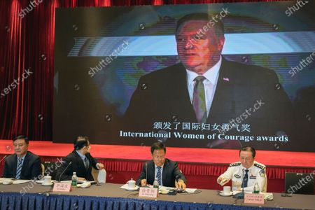 Xu Guixiang, a spokesperson for the Xinjiang northwestern region's government, second from right, and attendees sit near a screen showing former U.S. Secretary of State Mike Pompeo, during a press conference related to Xinjiang issues in Beijing, . China on Tuesday denounced a people's tribunal planned for the UK over allegations of genocide being committed against Uyghurs and other Turkic Muslim people in the Xinjiang region