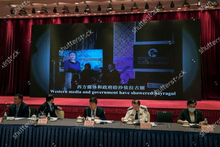 Xu Guixiang, a spokesperson for the Xinjiang northwestern region's government, center, and attendees sit near a screen showing former U.S. Secretary of State Mike Pompeo meeting with Sayragul Sauytbay, an Uyghur woman who have escaped from China after sent to the educational and training camp, during a press conference related to Xinjiang issues in Beijing, . China on Tuesday denounced a people's tribunal planned for the UK over allegations of genocide being committed against Uyghurs and other Turkic Muslim people in the Xinjiang region
