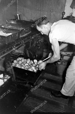 Crew of destroyer USS Breckinridge baking potato, United States, 1940.