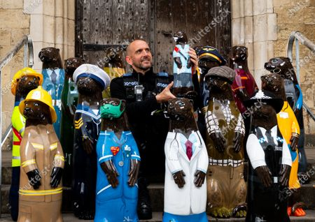 Officer Robert Window admires the collection of otter statues which have been designed to celebrate the role of key workers during the coronavirus pandemic in Winchester, Hants.  The statues will go on display throughout the city of Winchester which celebrate the efforts of our frontline workers, with roles including doctors, nurses, teachers, police and military as well as postmen, supermarket workers, construction workers and farmers.  At the end of June the statues will be auctioned to raise funds for local charity, Winchester Hospice.   The larger statues measure 3ft, with the smaller statues measuring 1.5 ft and go on display Saturday 22nd May 2021.
