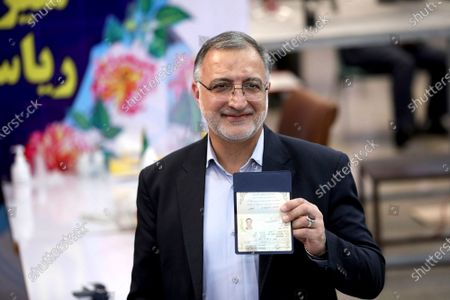 Former lawmaker Ali Reza Zakani shows an identification document to media while registering his candidacy for the upcoming presidential elections at the Interior Ministry in Tehran, Iran, . Iran named seven candidates Tuesday, May 15, for its June 18 presidential election, approving the candidacy of Zakani and hard-line cleric Ebrahim Raisi, while barring former parliament speaker Ali Larijani allied to the country's current president