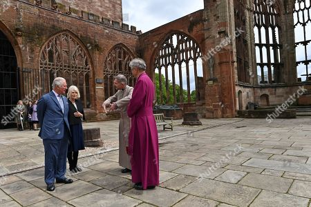 Stock Image of Prince Charles (L)and Camilla Duchess of Cornwall are accompanied by the Bishop of Coventry, Rev Christopher Cocksworth (R) and the Dean of Coventry Rev John Witcombe (2R) as they look at the ruins of the Old Cathedral during their visit to Coventry Cathedral in Coventry, central England on May 25, 2021, during the 59th anniversary of its Consecration year.