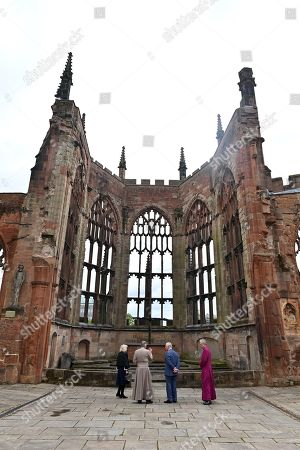 Prince Charles (2R) and Camilla Duchess of Cornwall are accompanied by the Bishop of Coventry, Rev Christopher Cocksworth (R) and the Dean of Coventry Rev John Witcombe (2L) as they look at the ruins of the Old Cathedral during their visit to Coventry Cathedral in Coventry, central England on May 25, 2021, during the 59th anniversary of its Consecration year.