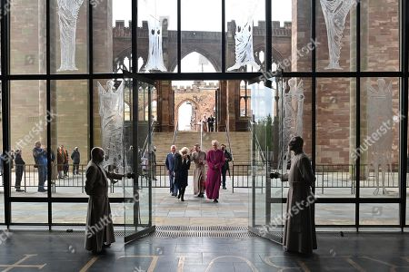 Stock Photo of Prince Charles (L) and Camilla Duchess of Cornwall are accompanied by the Bishop of Coventry, Rev Christopher Cocksworth (R) and the Dean of Coventry Rev John Witcombe (2R) as they walk from the ruins of the Old Cathedral to the new Coventry Cathedral in Coventry, central England on May 25, 2021, during the 59th anniversary of its Consecration year.