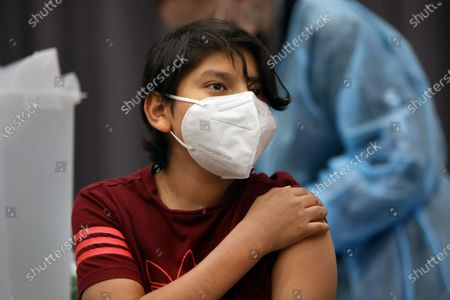 Stock Photo of San Pedro-May 24, 2021-Max Hernandez, age 12, gets vaccinated by Aida Flores, a visiting nurse from Austin, Texas, on May 24, 2021. San Pedro Senior High school is one of the Los Angeles County Unified schools providing coronavirus vaccines for children 12 and up.  (Carolyn Cole / Los Angeles Times)