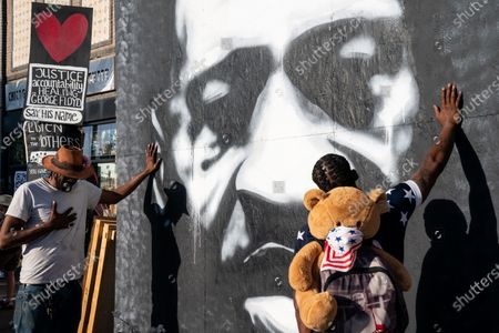 Jay Webb and Michael Wilson, both of Minneapolis puts their hands on a mural of the late George Floyd as they pay their respects during a visit the George Floyd Memorial Square on Tuesday, May 25, 2021 in Minneapolis, MN.