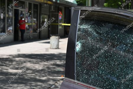 Stock Image of A shattered car window from a bullet at a crime scene involving a daytime shooting at Adam Clayton Powell Jr. Boulevard and 115th Street in the Harlem neighborhood of New York.
