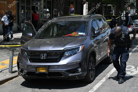 Police investigate a crime scene involving a daytime shooting at Adam Clayton Powell Jr. Boulevard and 115th Street in the Harlem neighborhood of New York.