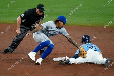 Tampa Bay Rays' Brett Phillips (35) steals second base ahead of the tag by Kansas City Royals shortstop Adalberto Mondesi during the third inning of a baseball game, in St. Petersburg, Fla. Making the call is umpire Mark Carlson